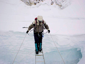 Nawang carefully crossing a huge crevasse in the deadly Khumbu Icefall.
